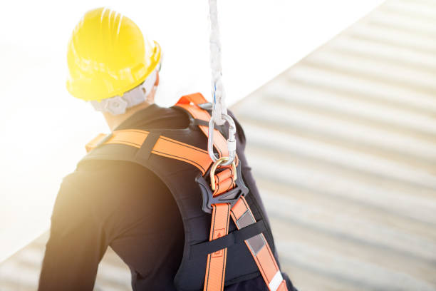 industrial worker with safety protective equipment loop and harness hanging at his back - protection stock photos and pictures