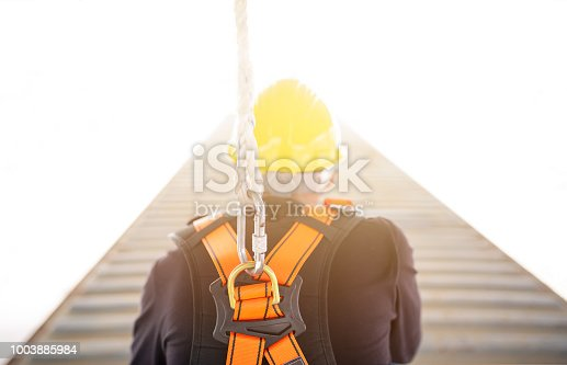 istock Industrial Worker with safety protective equipment loop and harness hanging at his back 1003885984