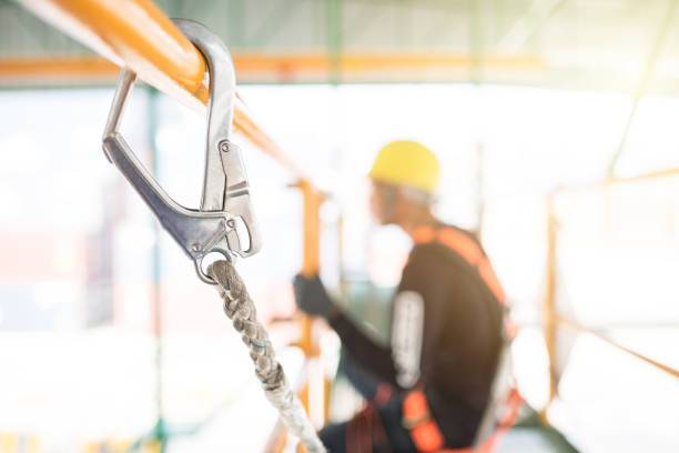 Industrial Worker with safety protective equipment loop hanging on the bar besides safety in factory concept for using in graphic media, websites, brochures, presentation in organization, etc. safety harness stock pictures, royalty-free photos & images