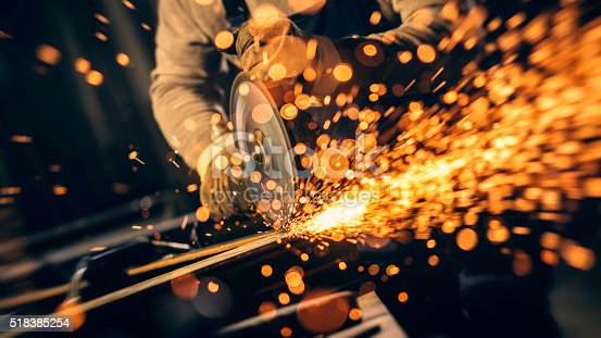Metal worker cutting a metal objects with circular saw in small workshop.