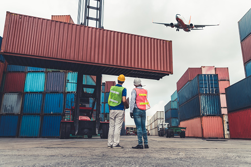 Industrial worker works with co-worker at overseas shipping container port . Logistics supply chain management and international goods export concept .
