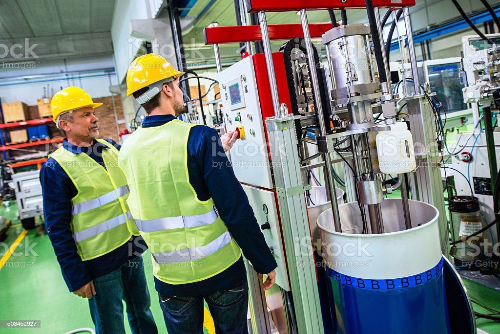 Industrial Workers Controling Machine in the Factory stock photo
