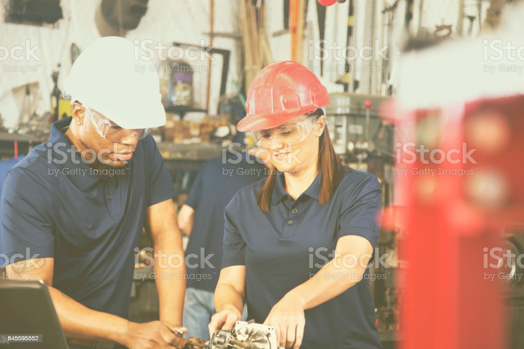 Industrial workers, machinists repair equipment together in factory. stock photo