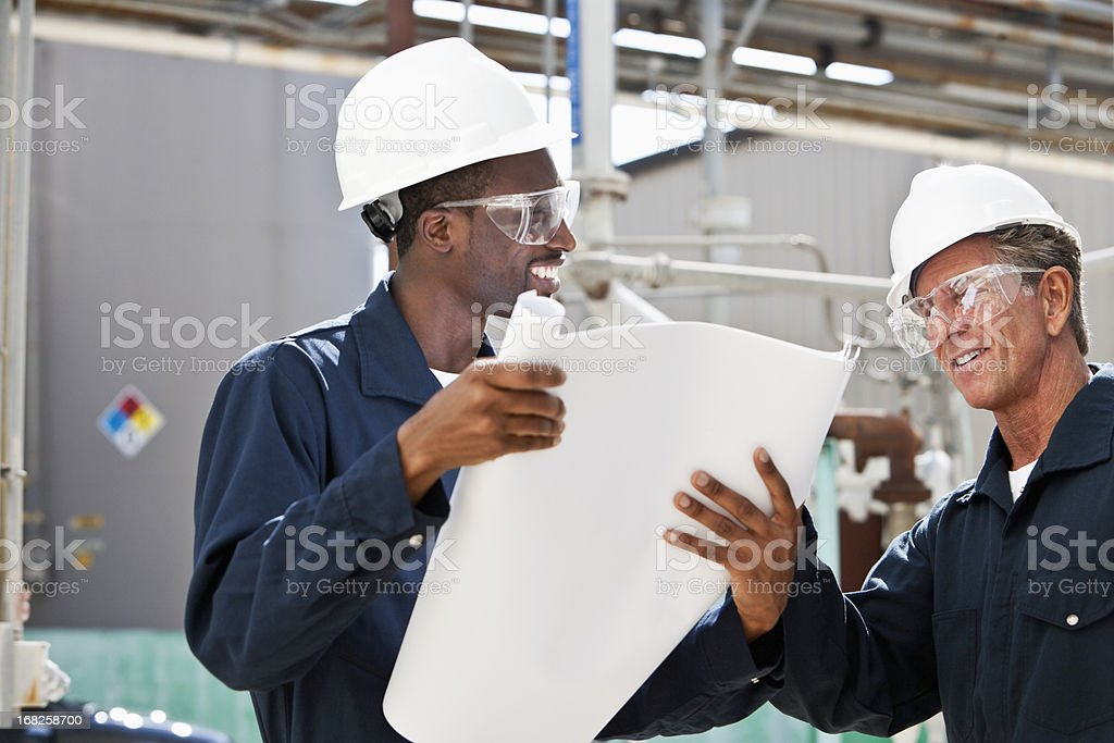 Industrial workers reviewing plans stock photo