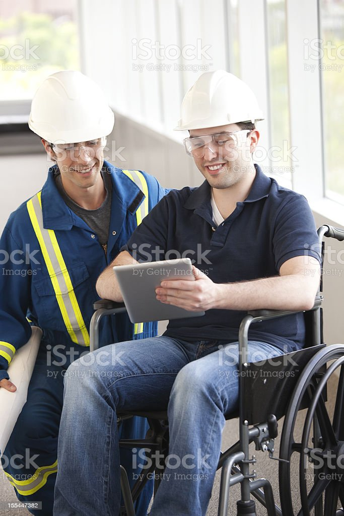 Industrial Workers With A Wheelchair and Tablet stock photo