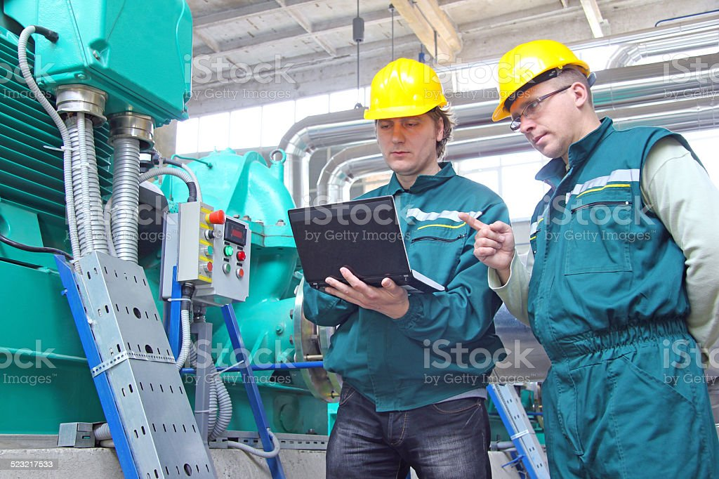 Industrial workers with notebook stock photo