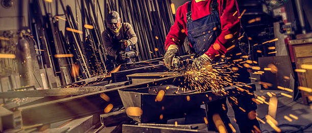 Industrial workers with work tools Metal workers cutting a metal objects with circular saws in small workshop. metal worker stock pictures, royalty-free photos & images