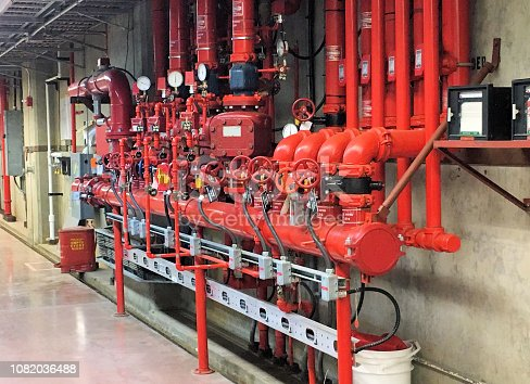 An automatic system of red metal pipes, sensors and valves for fire safety at an industrial workplace.