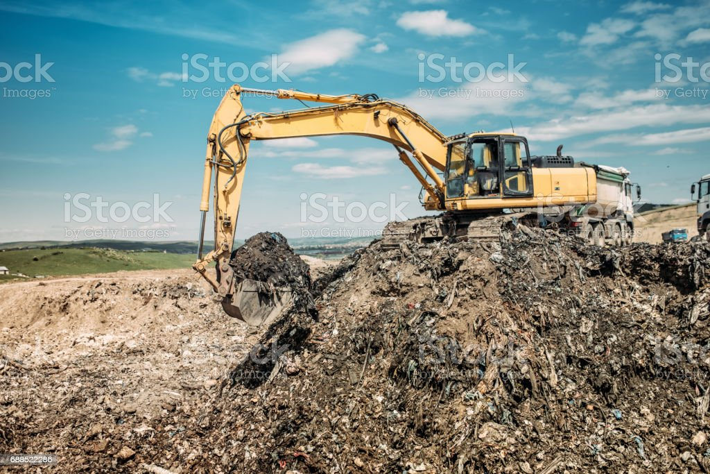 industrial works with excavator using heavy duty scoop at garbage dumpsite stock photo