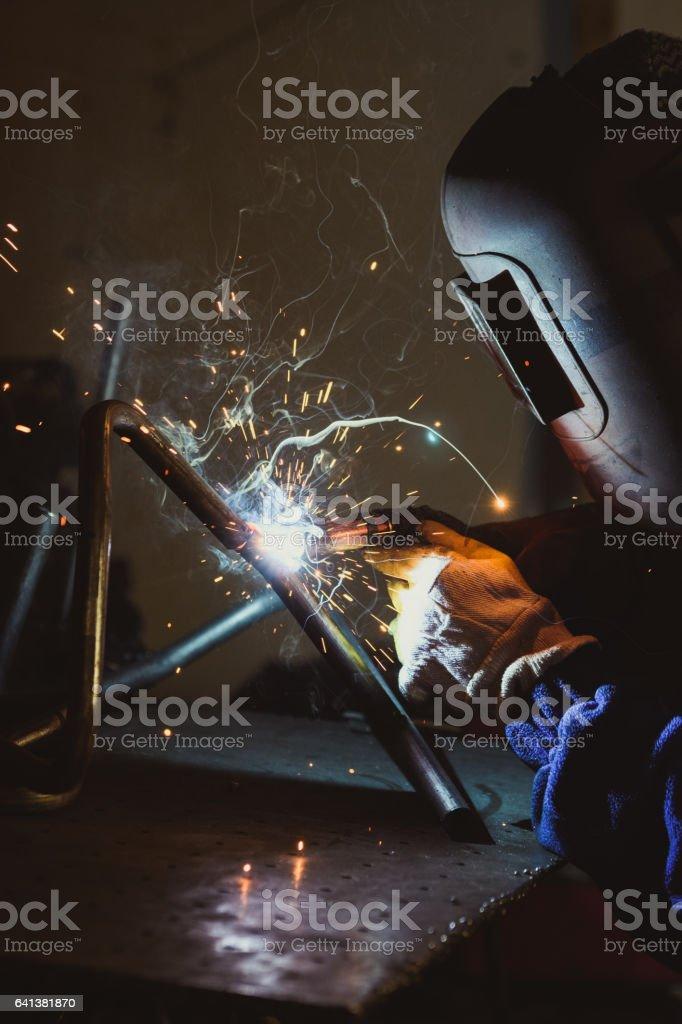 Industrial workshop man welding round pipe on a metal work table,...