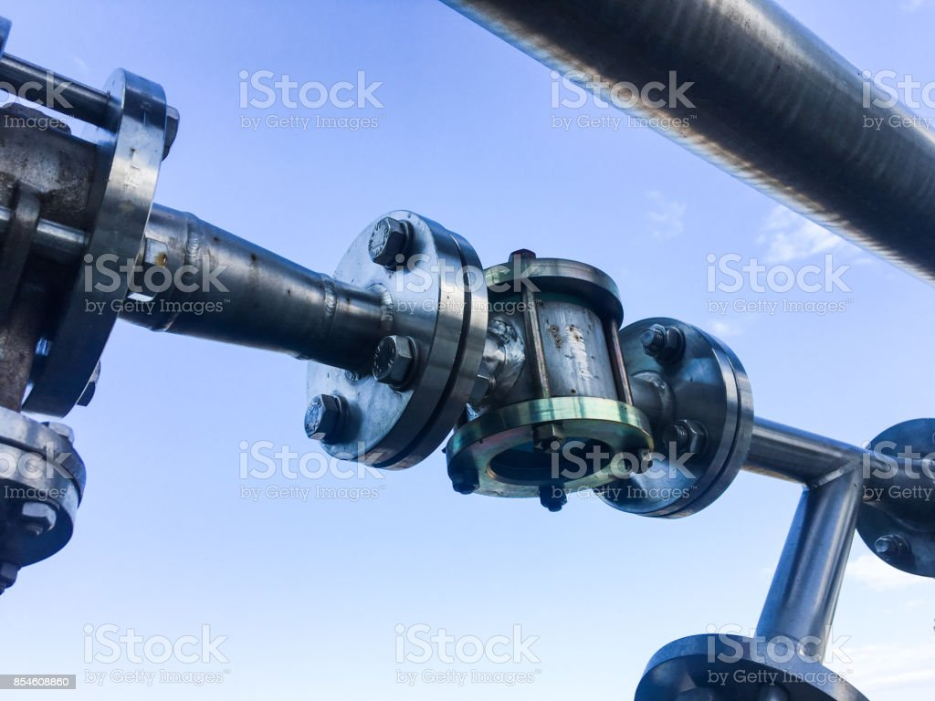Industrial zone, Steel pipelines , valves and flange against blue sky stock photo