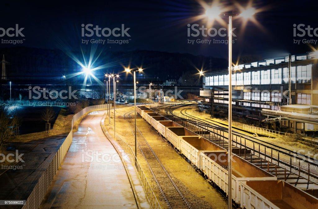 Industriebahnhof Rangierbahnhof bei Nacht mit vielen Lichtern und Waggons auf einem Abstellgleis in einer Industrieanlage mit violetter Optik stock photo