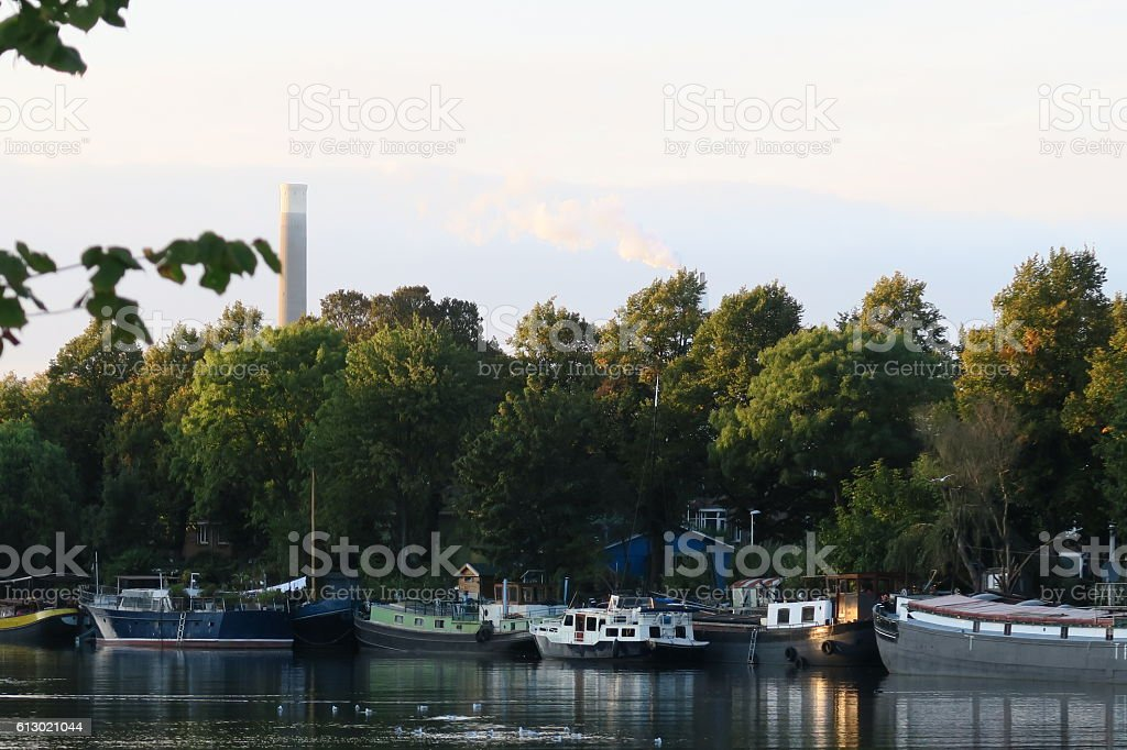industrual chimneys smoking next to canal barges at sunset stock photo