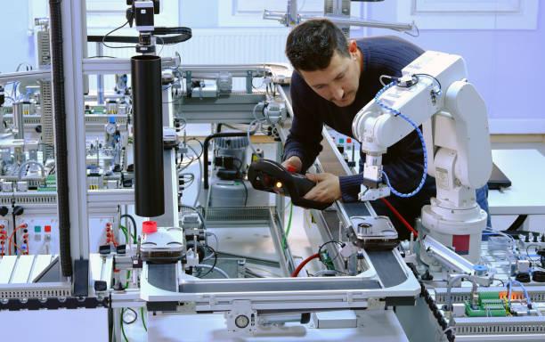 concepto de la industria 4.0: un ingeniero está programando brazo robótico - robótica fotografías e imágenes de stock