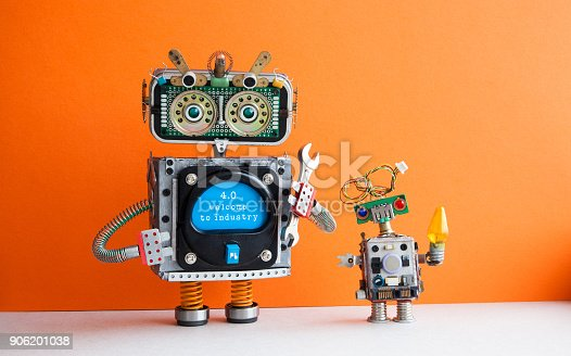 istock Industry 4.0 concept. Big IT specialist robot with hand wrench and small robotic cyborg. Welcome to the new economic future message on blue display. Orange wall background 906201038