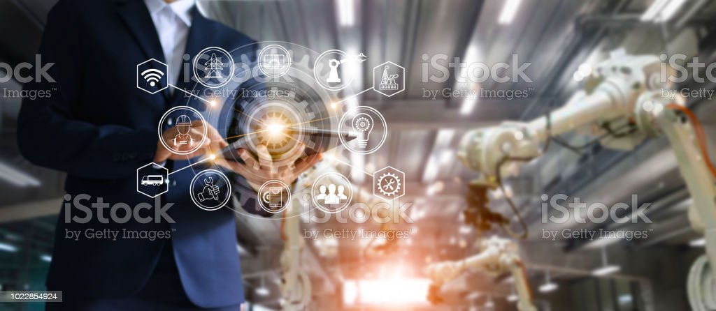 Industry, 4.0 concept, Icon flow automation and data exchange in manufacturing technology, Manager industrial engineer using tablet check and control automation robot arms machine in intelligent factory industrial on system software interface. Welding rob stock photo