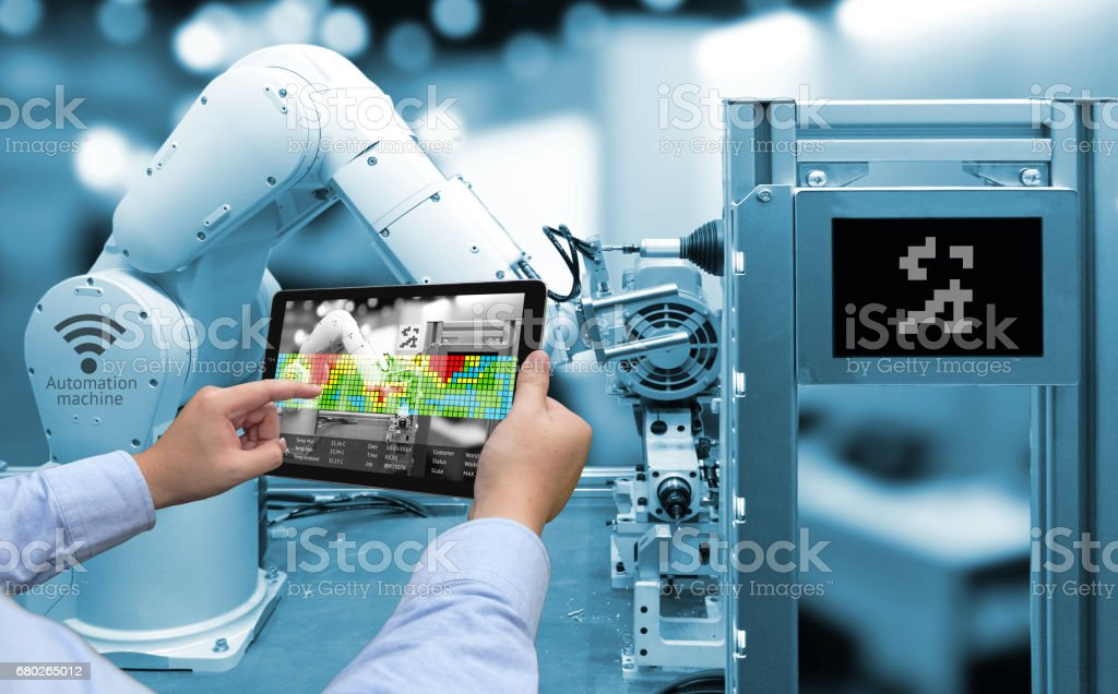 Industry 4.0 concept .Man hand holding tablet with Augmented reality screen software and blue tone of automate wireless Robot arm in smart factory background stock photo