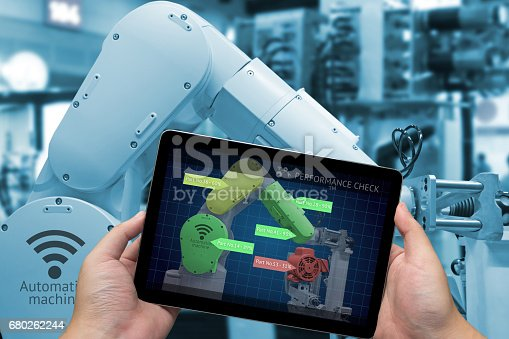istock Industry 4.0 concept . Man hand holding tablet with performance check screen software and blue tone of automate wireless Robot arm in smart factory background 680262244