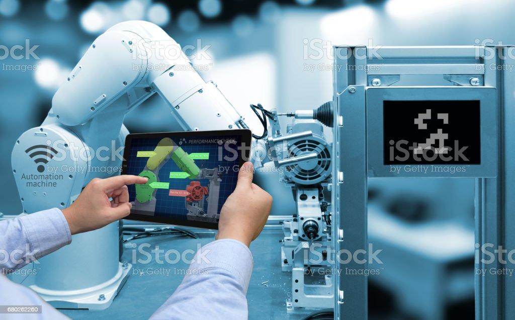 Concepto de industria 4.0. Hombre mano holding de la tableta con rendimiento cheque pantalla software y azul tono de automatizar inalámbrico brazo Robot en el fondo de la fábrica inteligente - foto de stock