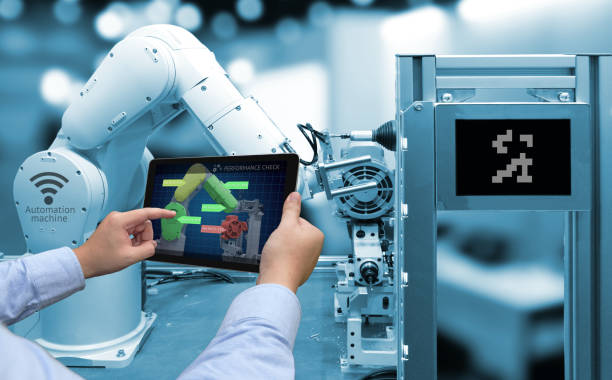 industry 4.0 concept . man hand holding tablet with performance check screen software and blue tone of automate wireless robot arm in smart factory background - computer aided manufacturing stock photos and pictures