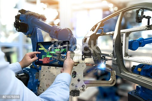 istock Industry 4.0 concept . Man hand holding tablet with performance check screen software and automate wireless Robot arm in automobile smart factory background. 821575316
