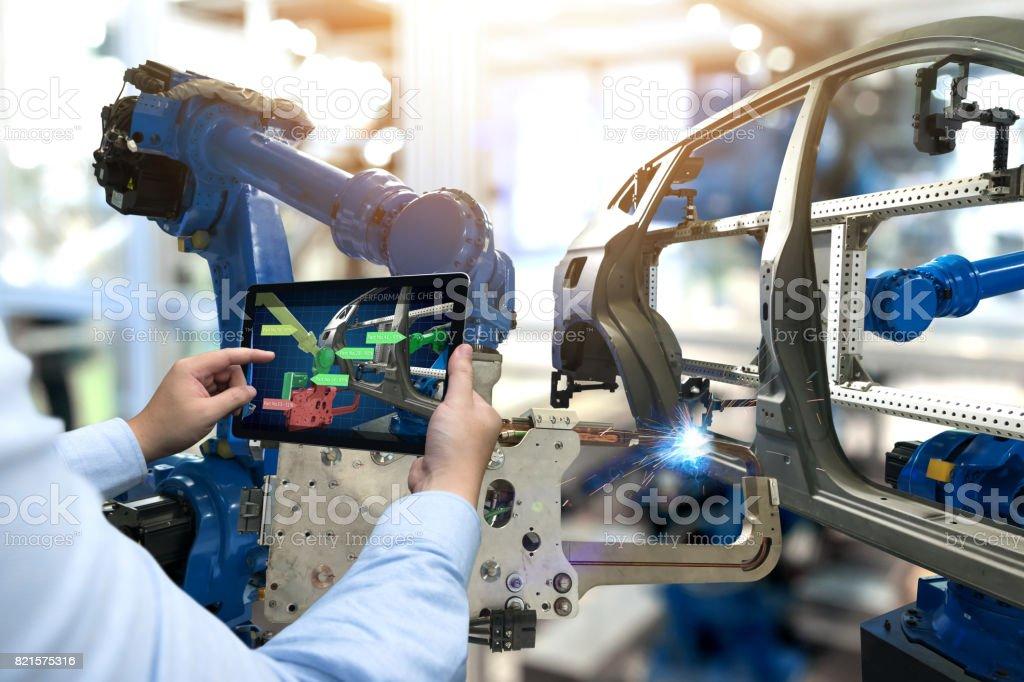 Industrie 4.0-Konzept. Mann Hand Holding Tablet mit Leistung überprüfen Sie Screen-Software und drahtlose Roboterarm in intelligente Automobilfabrik Hintergrund zu automatisieren. – Foto