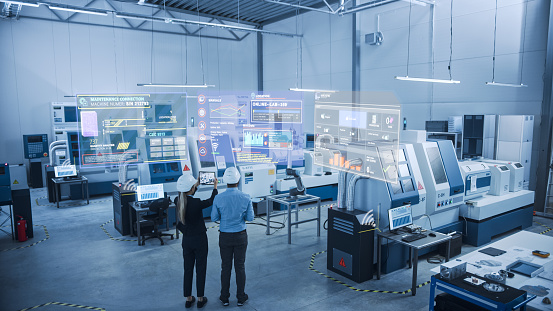 Industry 4.0 Factory: Two Engineers Uses Digital Tablet Computer with Augmented Reality Software to Connect with High-Tech Machinery, Robot Arm and Visualize Maintenance and Diagnostics of Equipment