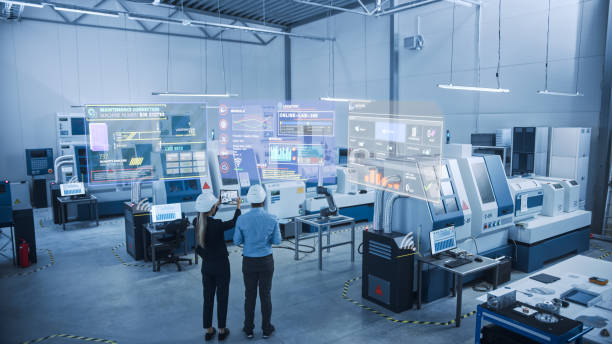 Industry 4.0 Factory: Two Engineers Uses Digital Tablet Computer with Augmented Reality Software to Connect with High-Tech Machinery, Robot Arm and Visualize Maintenance and Diagnostics of Equipment stock photo