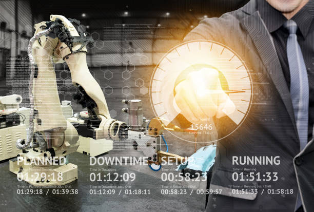 Industry 4.0 internet of things concept. Application UI screen and Man suit Engineer finger point to screen for control automation wireless robot machine arm background in smart factory. stock photo