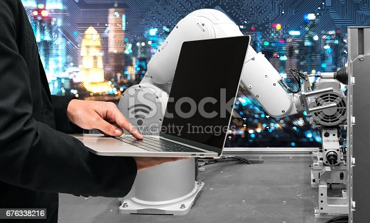 istock Industry 4.0 internet of things concept. Engineer finger point to black screen laptop for control automation wireless robot machine arm and circuit board industrial graphic background in smart factory 676338216