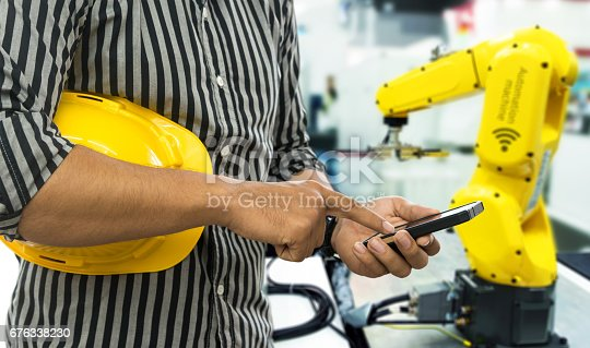 istock Industry 4.0 internet of things concept. Selective focus on Engineer finger point to smart phone for control blur robot machine arm background and yellow hat in smart factory. 676338230