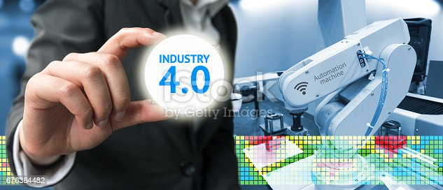 676364668 istock photo Industry 4.0 , Machine learning and artificial intelligence concept. Man suit hand holding Ai chipsets and blue tone of automate wireless Robot arm in smart factory background 676364482