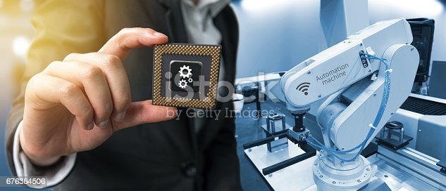 istock Industry 4.0 , Machine learning and artificial intelligence concept. Man suit hand holding Ai chipsets and blue tone of automate wireless Robot arm in smart factory background with flare light effect 676364506