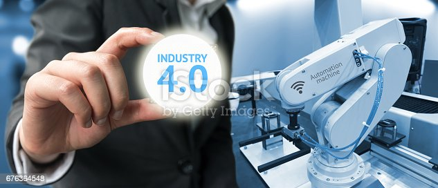 istock Industry 4.0 , Machine learning and artificial intelligence concept. Man suit hand holding Ai chipsets and blue tone of automate wireless Robot arm in smart factory background 676364548