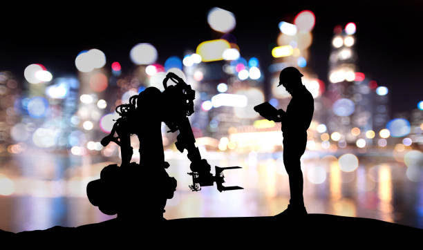 Industry 4.0 technology , artificial intelligence trend concept. Silhouette of engineer man control to heavy automation robot arm machine. Bokeh flare light effect with building background. stock photo