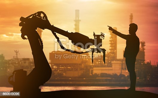 istock Industry 4.0 technology , artificial intelligence trend concept. Silhouette of business man point finger forward to heavy automation robot arm machine. Vivid sunset sky and smart factory background. 860649096
