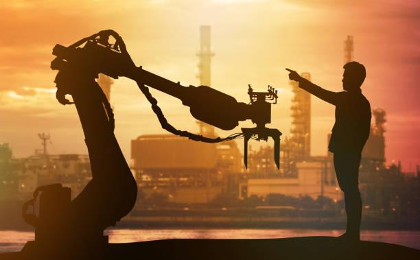 4.0 tecnología, inteligencia artificial concepto de tendencia. Silueta de negocios hombre punto dedo a pesadas automatización robot brazo máquina. Viva cielo al atardecer y fondo de fábrica inteligente. - foto de stock