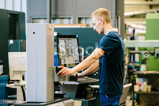 istock Industry 4.0: young engineer control his work on a CNC machine 1156642049