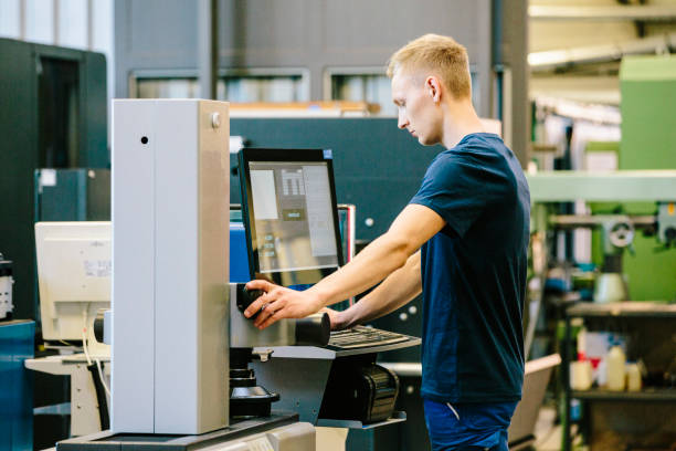 Industry 4.0: young engineer control his work on a CNC machine stock photo