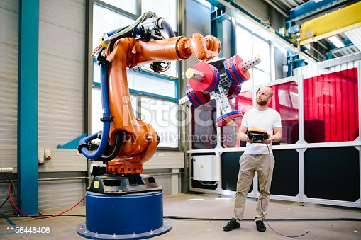 1022530836 istock photo industry 4.0: Young engineer works at a robotic arm 1156448406