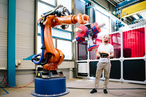 istock industry 4.0: Young engineer works at a robotic arm 1156448406