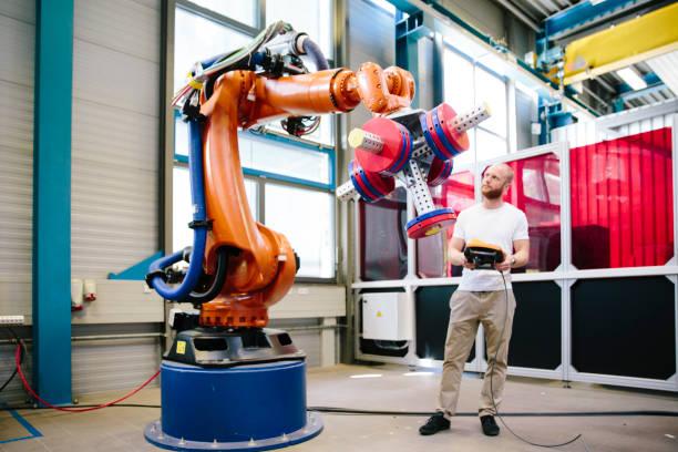 industrie 4,0: jonge ingenieur werkt bij een robotarm - robot engineer stockfoto's en -beelden