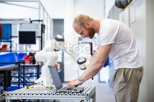 istock industry 4.0: Young engineer works at a robotic arm 1156496515