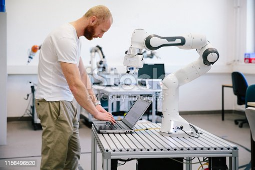 istock industry 4.0: Young engineer works at a robotic arm 1156496520