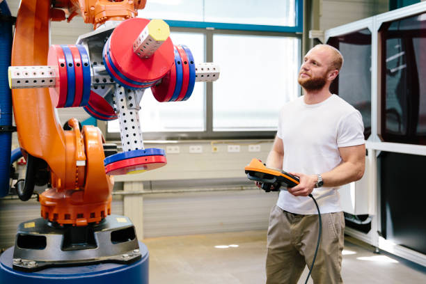 industry 4.0: Young engineer works at a robotic arm stock photo