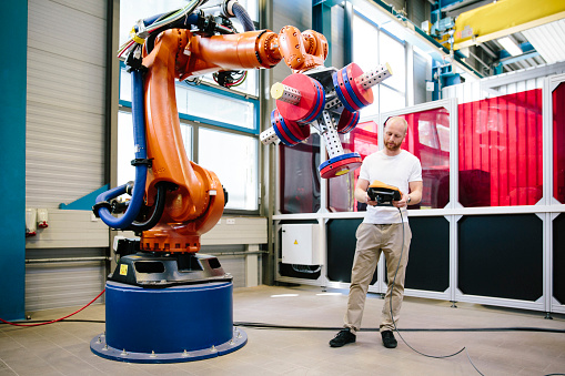 istock industry 4.0: Young engineer works at a robotic arm 1157298016