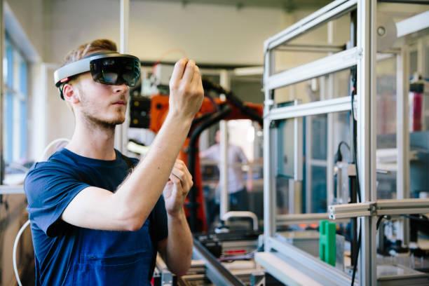 industry 4,0: genç mühendis baş monte ekran ile çalışır - sanal gerçeklik stok fotoğraflar ve resimler