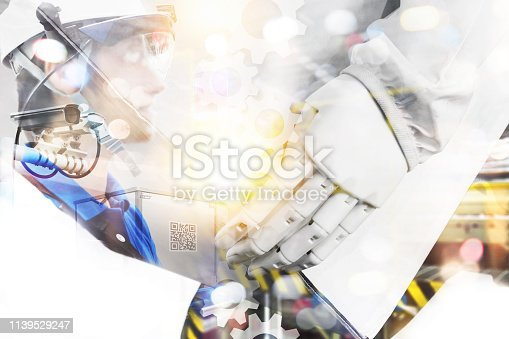 istock Industry 4.0,Augmented reality and smart logistic concept. Hand holding tablet with AR application for check order pick time in smart factory warehouse.Man use AR glasses and qr code box background. 1139529247