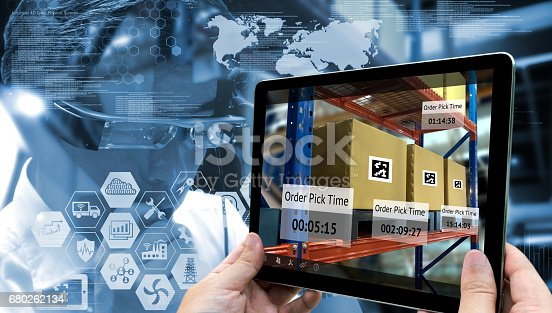 istock Industry 4.0,Augmented reality and smart logistic concept. Hand holding tablet with AR application for check order pick time in smart factory warehouse.Man use AR glasses and infographic background. 680262134