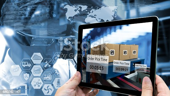 istock Industry 4.0,Augmented reality and smart logistic concept. Hand holding tablet with AR application for check order pick time in smart factory warehouse.Man use AR glasses and infographic background. 680262142